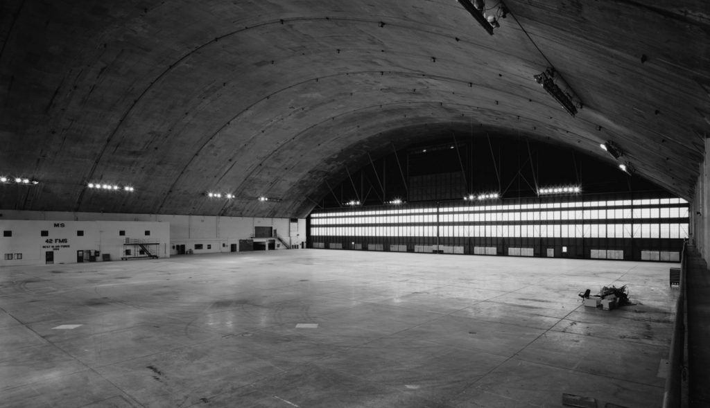 The DET hangar, black and white image of cavernous interior of large aircraft hangar.